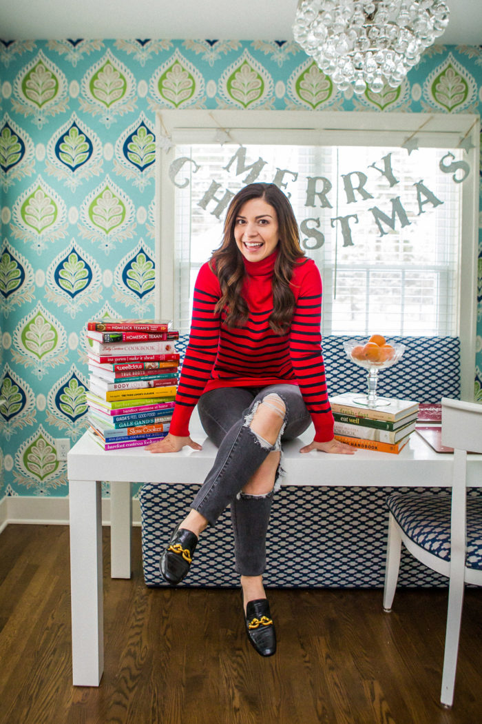 holiday dinner ideas holidays at home | Holiday Dinner Ideas for a Small Group by popular Michigan life and style blog, The HSS Feed: image of a woman sitting on a table with a Pottery Barn Kids Merry Christmas Glitter Garland hanging in the background and wearing a Banana Republic Luxespun Boxy T-Shirt, Levi's 721 High Rise Skinny Women's Jeans, and Tory Burch JESSA LOAFER.