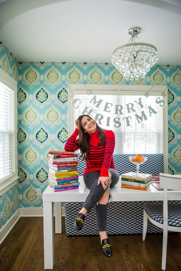 holiday dinner ideas for a small group | Holiday Dinner Ideas for a Small Group by popular Michigan life and style blog, The HSS Feed: image of a woman sitting on a table with a Pottery Barn Kids Merry Christmas Glitter Garland hanging in the background and wearing a Banana Republic Luxespun Boxy T-Shirt, Levi's 721 High Rise Skinny Women's Jeans, and Tory Burch JESSA LOAFER.