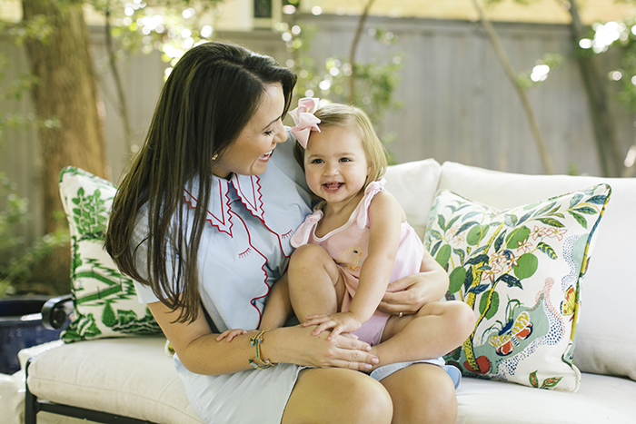 Kimberly Whitman Moms with Style | Kimberly Schlegel Whitman by popular Michigan life and style blog, The HSS Feed: image of Kimberly Schlegel Whitman sitting outside and holding her daughter on her lap.