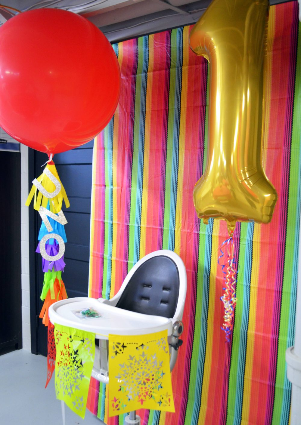 Fiesta Birthday Party by popular Michigan lifestyle blog, The HSS FEED: image of a highchair decorated with papel flags, a large red ballon, a large gold #1 balloon and a colorful stripe backdrop.