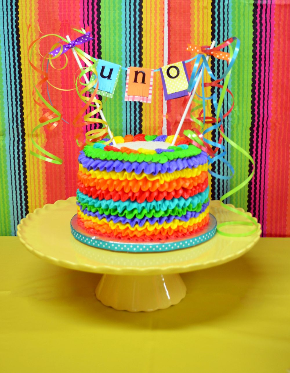 Fiesta Birthday Party by popular Michigan lifestyle blog, The HSS FEED: image of a fiesta birthday cake with an Uno cake topper.