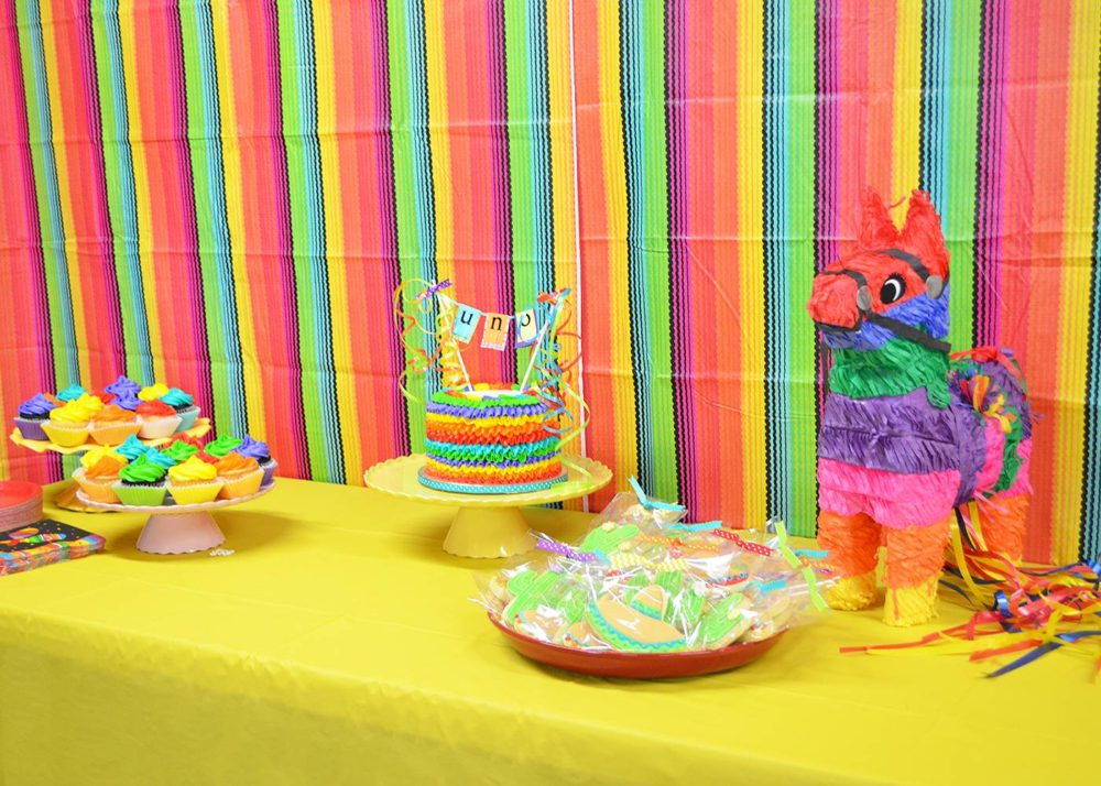 Fiesta Birthday Party by popular Michigan lifestyle blog, The HSS FEED: image of a fiesta dessert table with a birthday cake, sombrero and cactus sugar cookies, a donkey pinata, and cupcakes.
