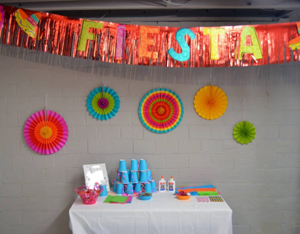 Fiesta Birthday Party by popular Michigan lifestyle blog, The HSS FEED: image of a Fiesta banner, colorful pinwheels, and a craft table.