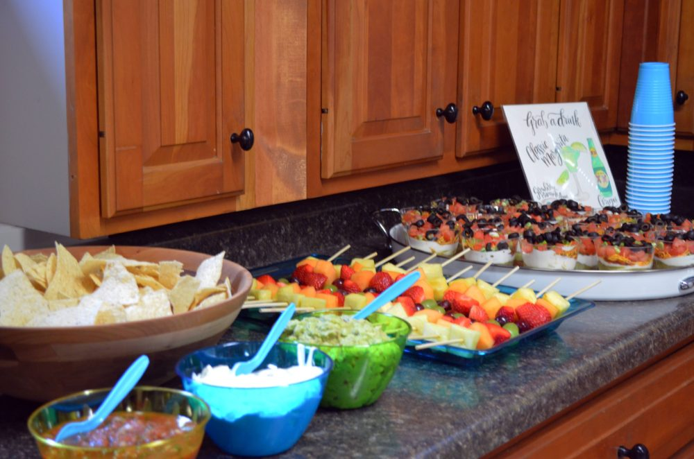 Fiesta Birthday Party by popular Michigan lifestyle blog, The HSS FEED: image of a tortilla chips, guacamole, salsa, sour cream, fruit kabobs, and 7 layer dip cups,