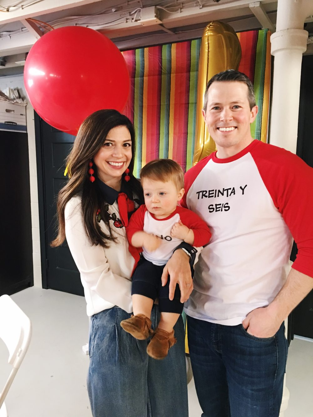 Fiesta Birthday Party by popular Michigan lifestyle blog, The HSS FEED: image of a mom and dad holding their 1 year old son together.
