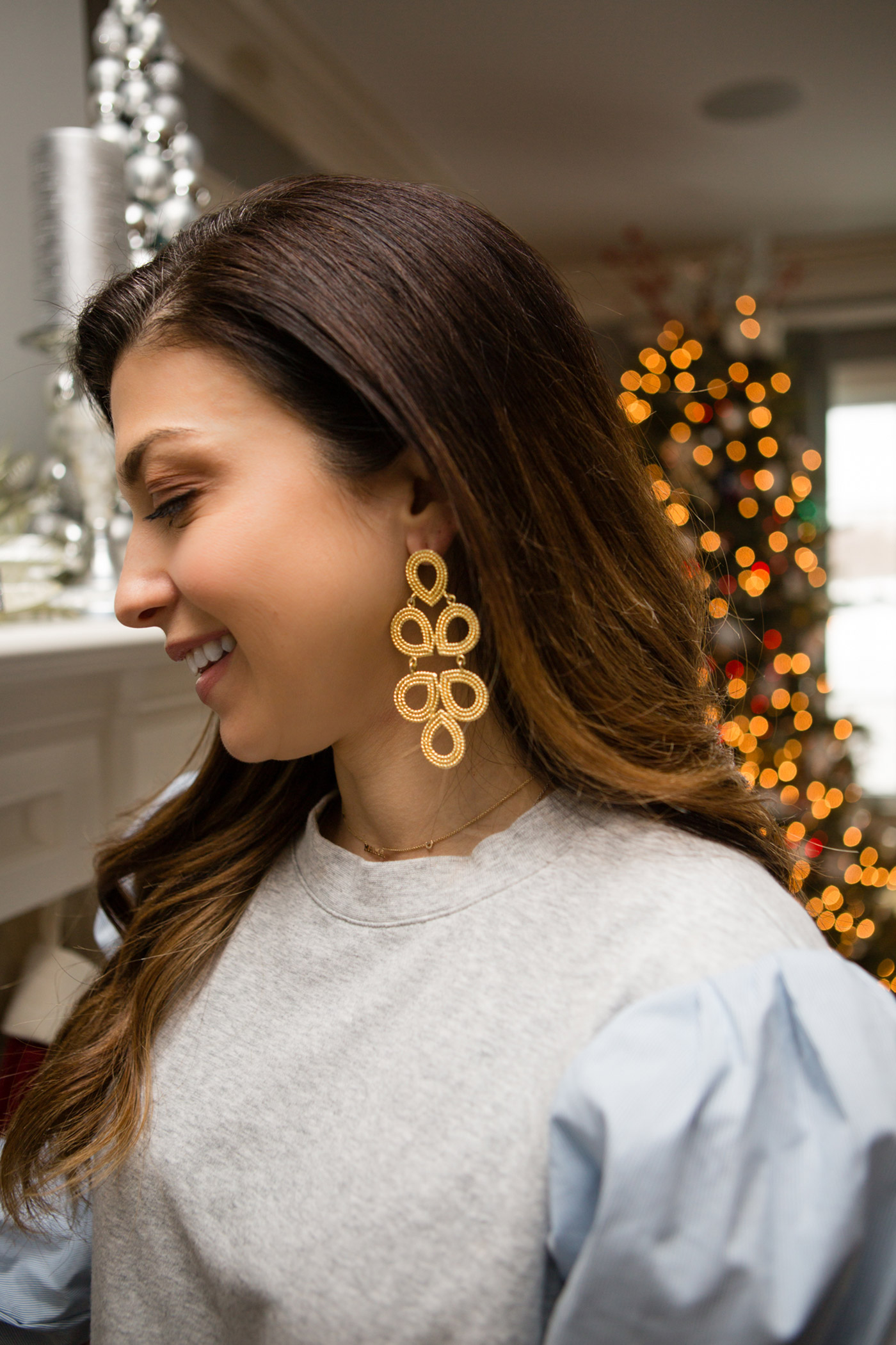 Lisi Lerch Earrings by popular Michigan fashion blog, The HSS Feed: image of a woman wearing Lisi Lerch earrings and hanging stockings on her fireplace mantle.