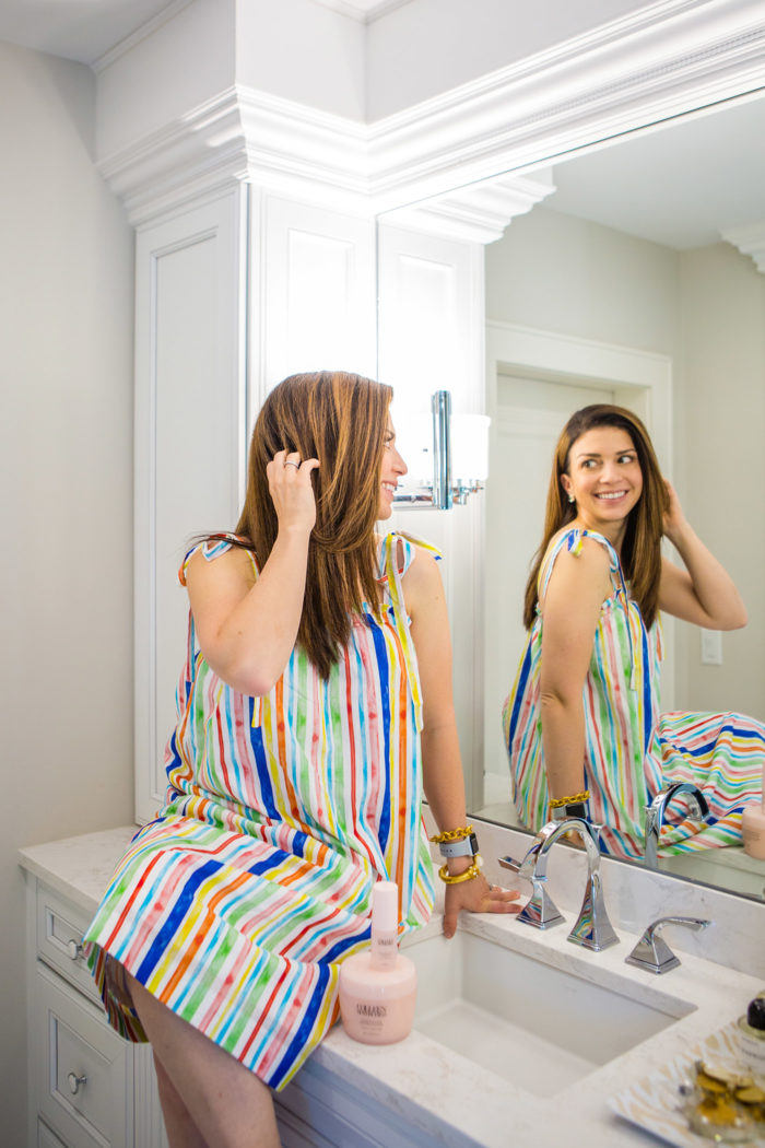 Colleen Rothschild Hair Mask by popular Michigan beauty blog, The HSS Feed: image of a woman sitting on her bathroom counter next to the Colleen Rothschild Hair Care kit as she runs her fingers through her hair and looks at herself in the mirror.