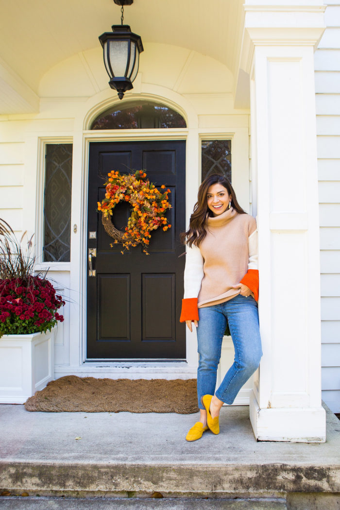 3 Cute and Trendy Thanksgiving Outfit Ideas featured by top US fashion blog, The HSS Feed.: image of a woman wearing an Amazon color block sweater, Banana Republic jeans, Kendra Scott earrings and Marc Fisher loafers.