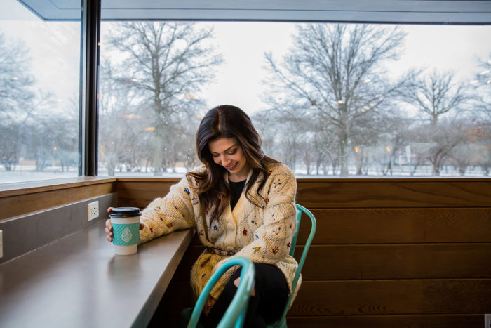Ways to Re-Inspire Creativity in the Workplace by popular Michigan lifestyle blog, The HSS Feed: image of a woman wearing a Zara  LIMITED EDITION EMBROIDERED CARDIGAN, Zara  MULTICOLORED JEWEL BELT, and Walmart distressed black jeans.