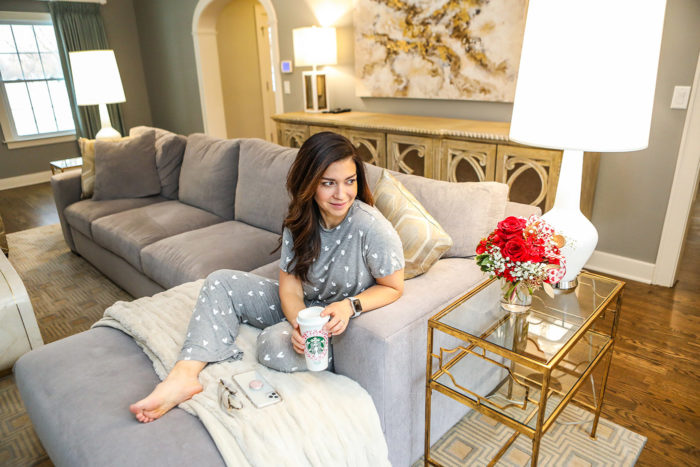 Best Things About February by popular Michigan lifestyle blog, The HSS Feed: image of a woman sitting on her couch while wearing Nordstrom Honeydew Intimates All American Pajamas and Prada PR 01UV glasses and holding a Etsy Lauren Mackenzie Decal Hello Gorgeous Starbucks Cup and smart phone with a Genuine Rose Quartz Popsockets.