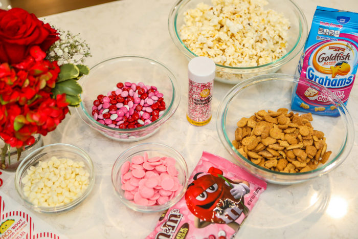 Valentine Treats for Kids by popular Michigan lifestyle blog, The HSS Feed: image of m&m's, white chocolate chips, Goldfish Grahams, popcorn, sprinkles and pink candy melts in clear glass bowls.