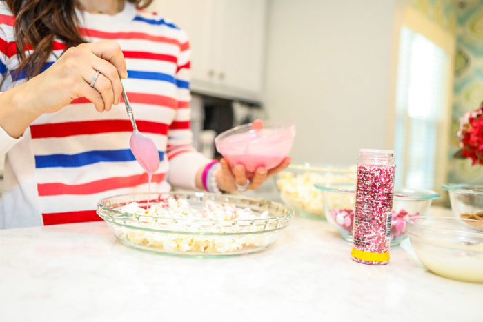 Valentine Treats for Kids by popular Michigan lifestyle blog, The HSS Feed: image of a woman sitting on her kitchen counter and wearing a Banana Republic stripe sweater, Target Wild Fable Women's High-Rise Distressed Cropped Mom Jeans, and Rothy's Petal Pink Solid flat and drizzling melted pink chocolate onto popcorn.