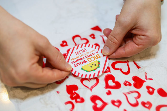 Valentine Treats for Kids by popular Michigan lifestyle blog, The HSS Feed: image of a woman placing a Etsy Chickabug Valentine's Day Stickers - TACO 'bout a Good Friend on a Amazon Boao Valentine treat bag.