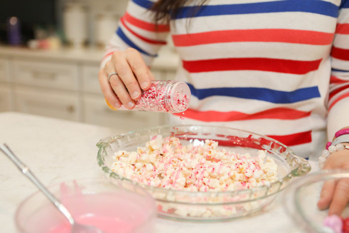 Valentine Treats for Kids by popular Michigan lifestyle blog, The HSS Feed: image of a woman sitting on her kitchen counter and wearing a Banana Republic stripe sweater, Target Wild Fable Women's High-Rise Distressed Cropped Mom Jeans, and Rothy's Petal Pink Solid flat and putting red white and pink sprinkles on some popcorn.