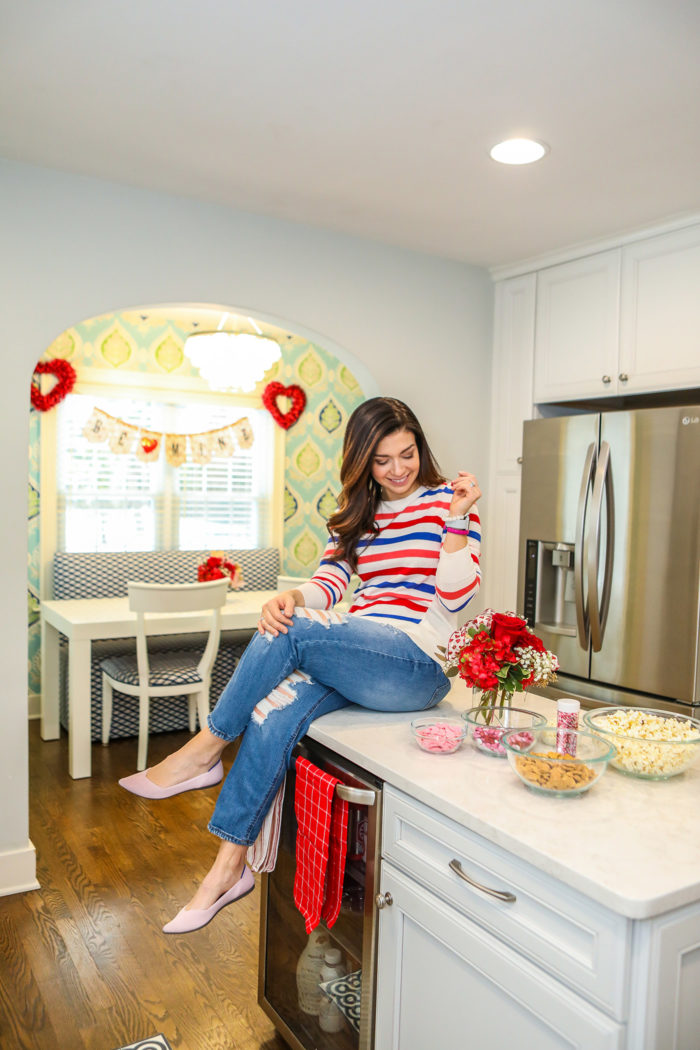 Valentine Treats for Kids by popular Michigan lifestyle blog, The HSS Feed: image of a woman sitting on her kitchen counter and wearing a Banana Republic stripe sweater, Target Wild Fable Women's High-Rise Distressed Cropped Mom Jeans, and Rothy's Petal Pink Solid flat.