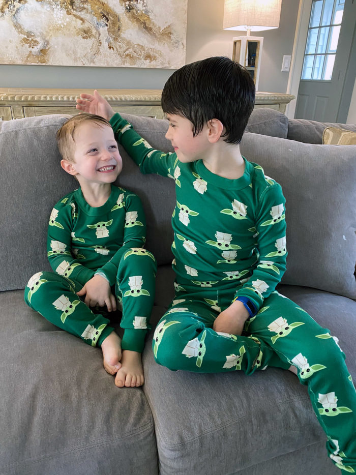 At Home Activities for Kids by popular Michigan lifestyle blog, The HSS Feed: image of two boys sitting on a couch and wearing matching Yoda pajamas.