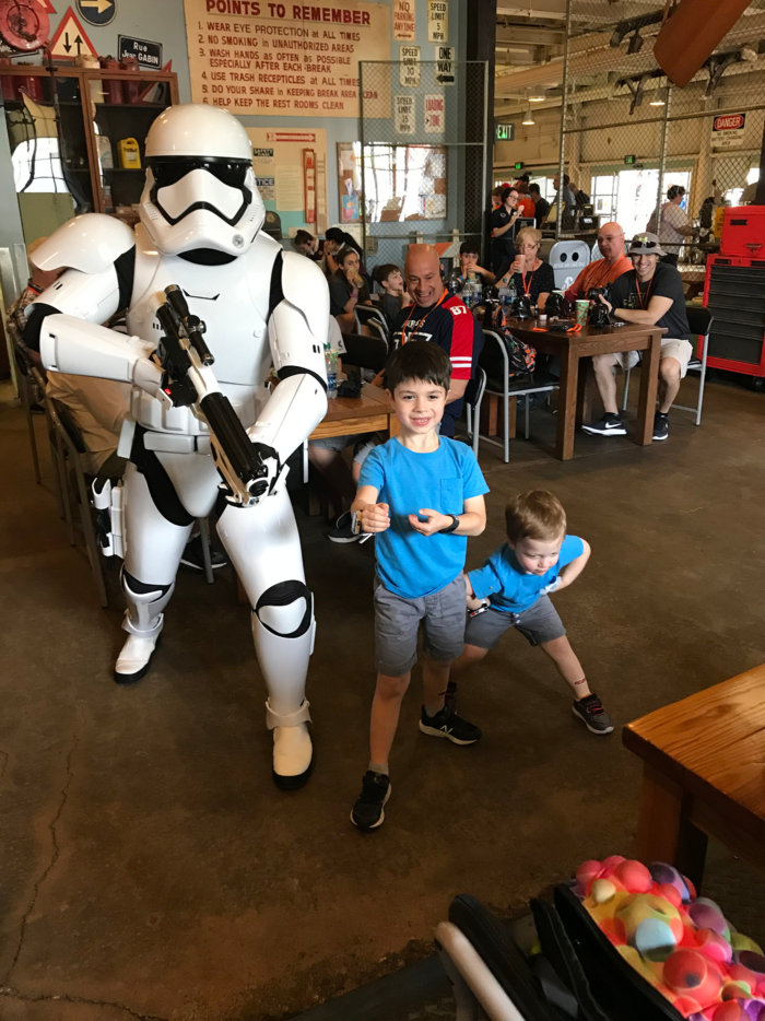 May the Fourth Star Wars Party | Star Wars Party Ideas by popular Michigan lifestyle blog, The HSS Feed: image of two young boys standing with a storm trooper.