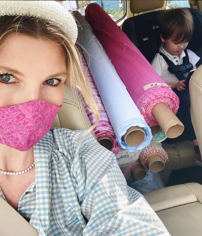 small business to shop BURU | Small Businesses to Shop Now by popular Michigan life and style blog: image of a woman wearing a pink face mask and riding in a car filled with rolls of fabric.